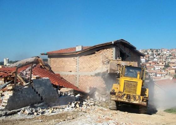Багер разрушава незаконна постройка.